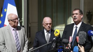 The head of France's top Muslim body Anouar Kbibech (right) speaks to journalists alongside his deputy Abdallah Zekri (left) and France's Interior Minister Bernard Cazeneuve in Paris on August 1, 2016.