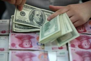 A bank clerk counts U.S. dollar banknotes on bundles of 100 Chinese yuan banknotes at a branch of a bank in Huaibei, Anhui province in this file photo dated April 26, 2012. REUTERS/Stringer