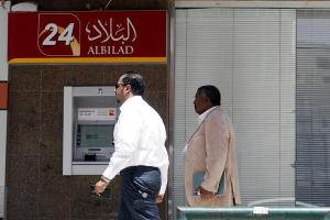 Men walk pass an automated teller machine outside Bank Al Bilad in Riyadh