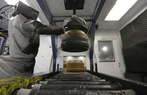 A robot paints brake drums at Webb Wheel Products in Cullman, Ala. (Dave Martin/Associated Press)