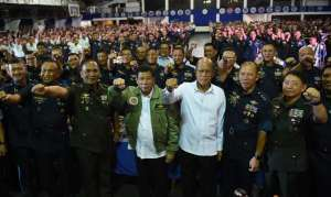 "Philippine President Rodrigo Duterte (C) wearing an air force jacket given to him as a gift, poses for photos with Defense Secretary Delfin Lorenzana (4th R) and Military chief General Ricardo Visaya (3rd L) and air force personnel prior to the traditional meal dubbed ""boodle fight"" during the 250th Presidential Airlift Wing Command anniversary celebrations at Villamor air base in Manila on September 13, 2016."
