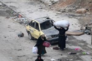 Women carry their belongings as they wait to be evacuated from a rebel-held sector of eastern Aleppo