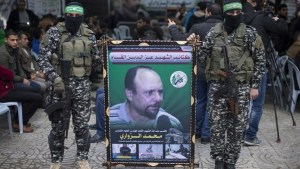 Members of the Izz ad-Din al-Qassam Brigades, the military wing of Hamas, hold a banner bearing a portrait of one of their leaders, Mohamed al-Zoari, who was killed in Tunisia, during a ceremony in his memory on December 18, 2016, in Gaza City.