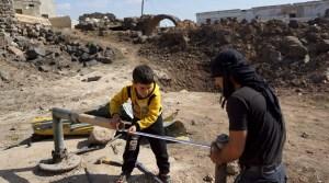 Civilians fix damaged water pipes in the rebel held al-Ghariyah al-Gharbiyah town, in Deraa province, Syria February 28, 2016.