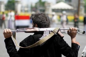 An armed man loyal to the Houthi movement holds his weapon as he gathers to protest against the elected government deciding to cut off the Yemeni central bank from the outside world, in the capital Sanaa, Yemen August 25, 2016.