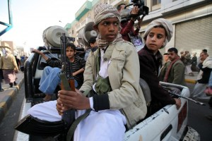 Boys who are part of the Houthi fighters hold weapons as they ride on the back of a patrol truck in Sanaa March 13, 2015.