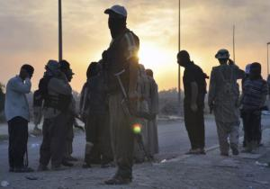 ISIS fighters stand guard at a checkpoint in the northern Iraq city of Mosul.- REUTERS