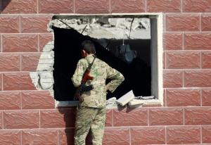A Sunni Arab fighter looks at a house which belonged to a Islamic State militant, in Rfaila village in the south of Mosul