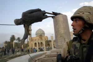 A U.S. soldier watches as a statue of Iraq's President Saddam Hussein falls in central Baghdad, April 9, 2003. REUTERS/Goran Tomasevic