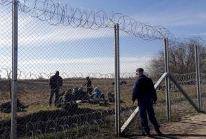 Migrants rest as a policeman watches them near Hungary's border fence on the Serbian side of the border near Morahalom