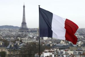 A city view shows the French flag above the skyline of the French capital as the Eiffel Tower and roof tops are seen in Paris, France, March 30, 2016. REUTERS/Benoit Tessier