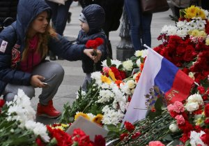 A woman places flowers at a memorial site for the victims of a blast in St. Petersburg metro, outside Tekhnologicheskiy Institut metro station in St. Petersburg