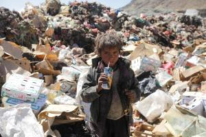A boy drinks expired juice on a pile of rubbish at landfill site on the outskirts of Sanaa, Yemen November 16, 2016. REUTERS/Mohamed al-Sayaghi