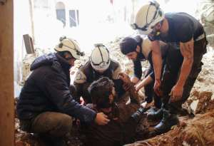 Members of the Syrian Civil Defence, also known as the White Helmets, remove a victim from the rubble of his house on April 8 in the southern Syrian city of Daraa.