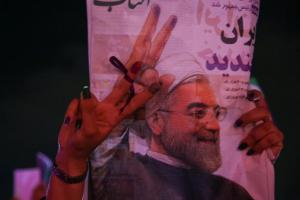 Supporter of Iranian president Hassan Rouhani holds his poster as she celebrates his victory in the presidential election, in Tehran