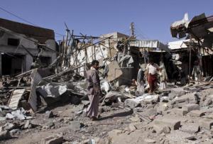 People inspect the site of an air strike in Yemen's northwestern city of Saada