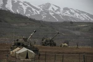 Israeli soldiers walk near mobile artillery units near the border with Syria in the Golan Heights