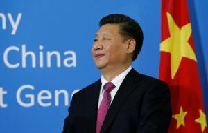 Chinese President Xi watches during a gift handover ceremony at the United Nations European headquarters in Geneva