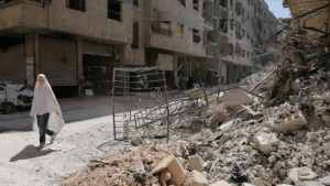 A girl walks past the rubble of a destroyed building down a street in the rebel-held Syrian town of Ayn Tarma, in the Ghouta area east of the capital Damascus, July 19, 2017.
