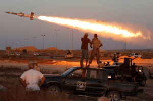 Fighters of Libyan forces allied with the UN-backed Government of National Accord (GNA) fire a rocket at ISIS militants in Sirte, Libya.