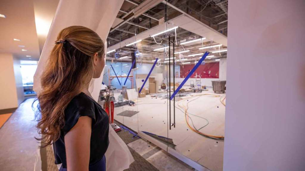 Photo of a woman holding a curtain back to look into a new lab.