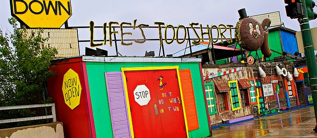 """Multicolored beach shop with sign: """"Slow Down. Life's Too Short"""""""