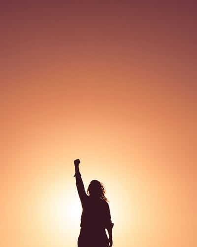 Woman standing in front of sunset with fist in the air