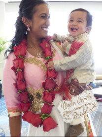 "Sister of Groom is decorated with rose garlands. Mom holds sig for son that reads: ""Uncle Ancil Here Comes Your Bride""."