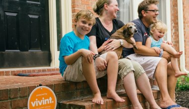 family sitting on the front step of their home with a dog