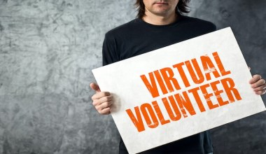 man holding banner that says virtual volunteer