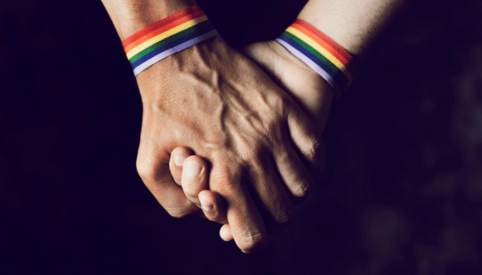 two people holding hands with pride bracelets on
