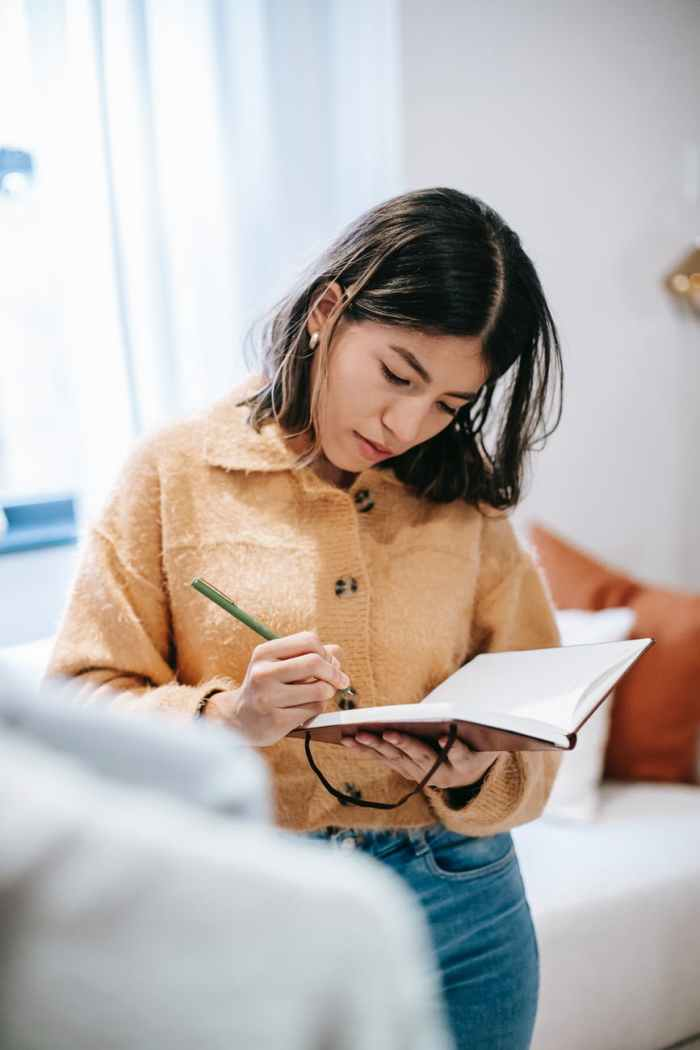 ethnic worker writing in notebook in house room