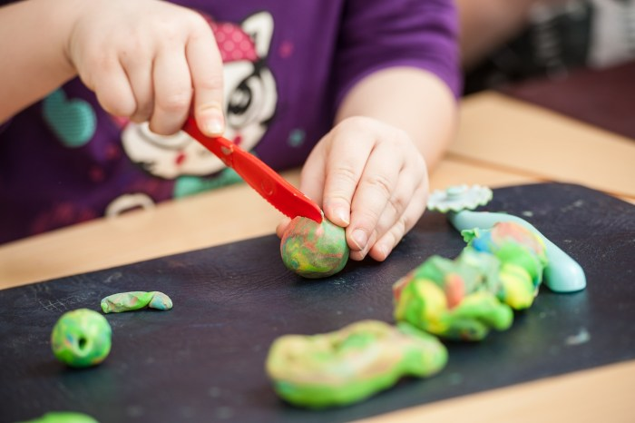 Child cutting play dough with plastic knife
