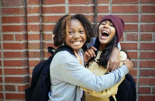 cheerful diverse schoolgirls embracing near brick wall