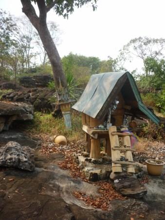 Ho Phi in der Nähe eines Tempels, außerhalb von Vientiane: Auch an manchen markanten Stellen, wie Steinen oder alten Bäumen findet man die Geisterhäuschen, um die jeweiligen Naturgeister zu besänftigen