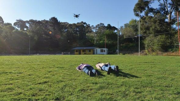 Duas pessoas (objetos de estudo) deitadas sobre a grama, enquanto ocorre uma footage por drone para analisar sinais vitais. University of South Australia. Engenharia 360.