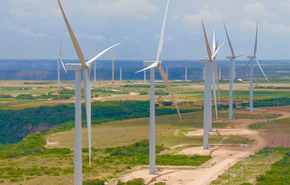 A imagem mostra uma usina eólica onshore, em terreno amplo para implementação.