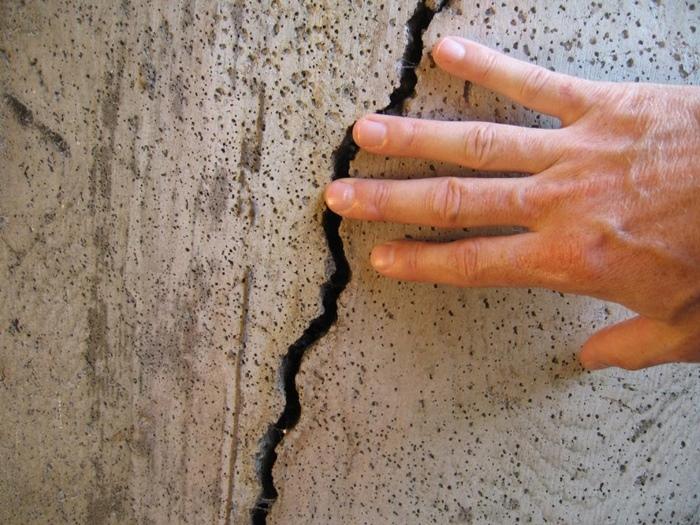 parede de concreto com uma mão sobre uma rachadura