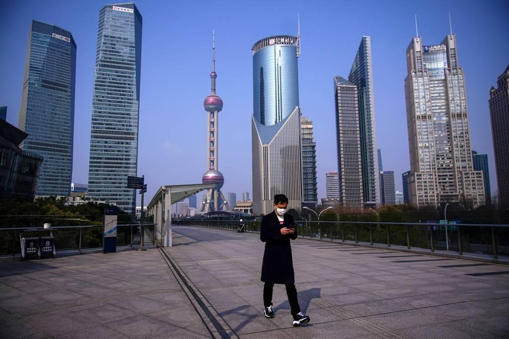 Homem andando em calçada de Xangai protegido com máscaras.