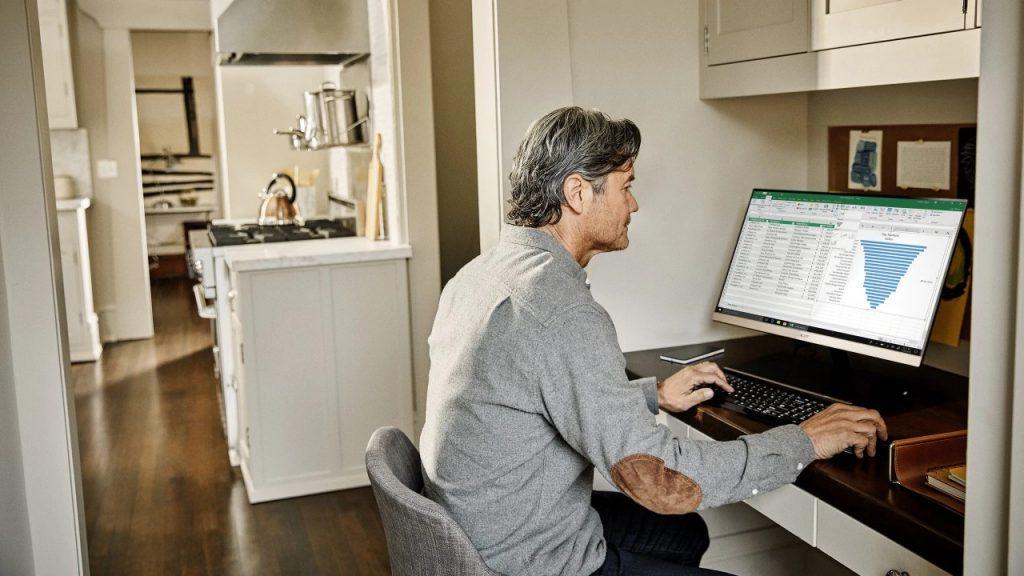 homem trabalhando em casa em uma mesa com computador