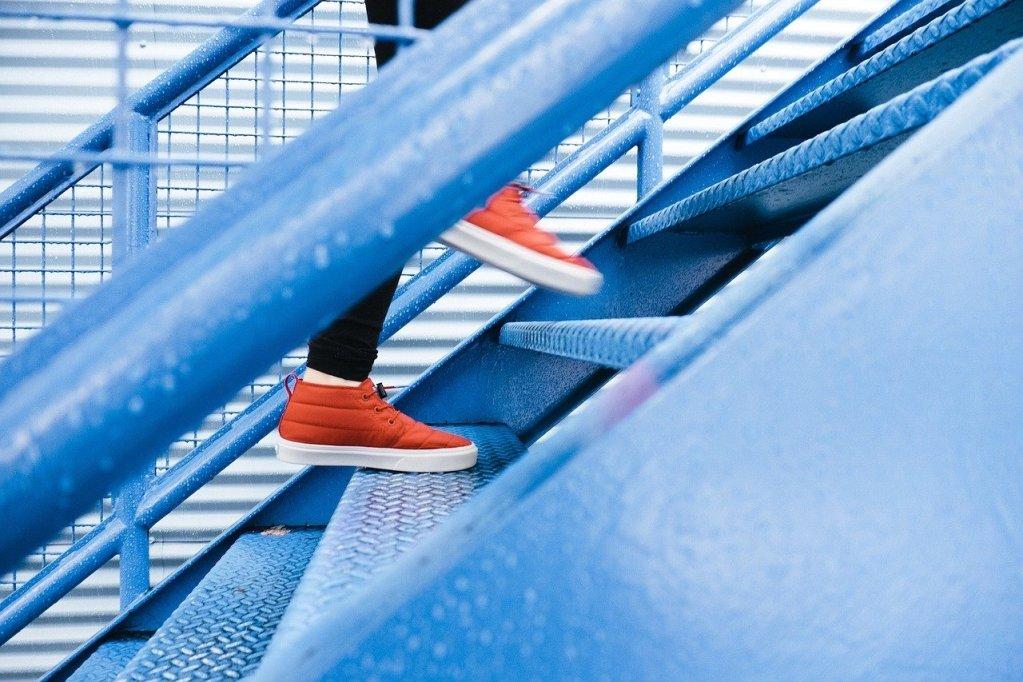 pés subindo escada representando alguém subindo na carreira