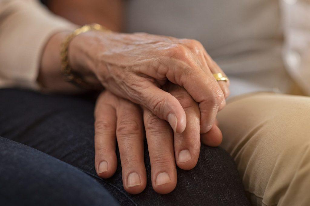 mãe idosa segurando a mão de filho jovem