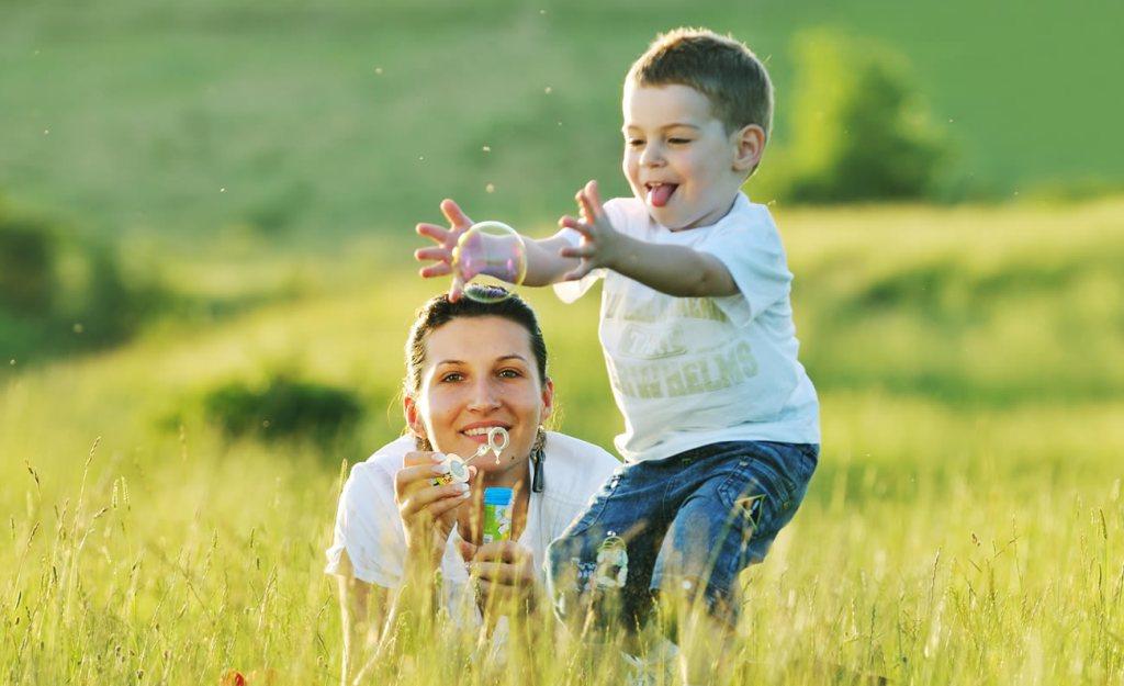 mãe brincando com seu filho em campo gramado