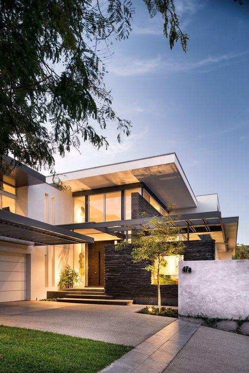 A imagem apresenta uma casa com estilo arquitetônico moderno, é entardecer e a casa está iluminada com lâmpadas amareladas