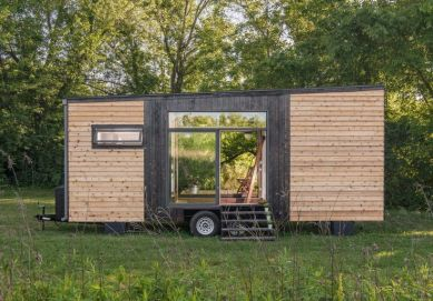 A modern 246 sq.ft. tiny house with Shou Sugi Ban cedar siding_ a dining table that seats eight people_ and a custom fold down deck and awning.