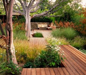 Looks like tons of work but gorgeous. Wooden pathway surrounded by grasses and trees.