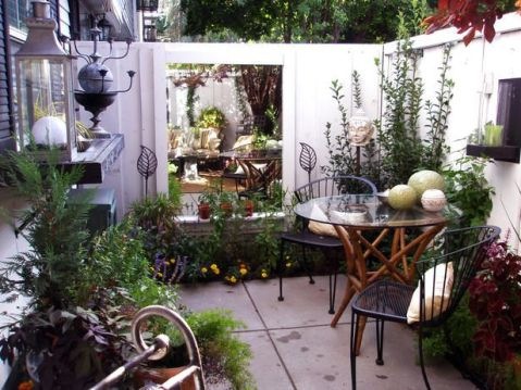 Small courtyard patio makes good use of large outdoor mirror_ small table set and perimeter planting. flowers and art pieces.