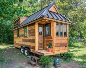 The Cedar Mountain Tiny House_ built by Nashville_based New Frontier Tiny Homes_ might look small on. With repurposed accessories_ shiplap walls_ subway tile_ and rich hardwood floors_