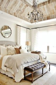French-country-linens-tufted-furniture-with-mirror-above-headboard