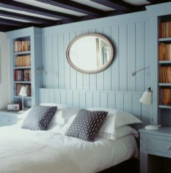 Bedroom with double bed and crisp white bed linen. The pale blue tongue and groove bedhead is built in against the wall and has integral bookshelves and bedside tables, Image: 13899844, License: Rights-managed, Restrictions: , Model Release: no, Credit line: Profimedia, Narratives